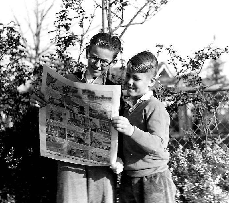 Kids looking at newspaper. in the 1950s.